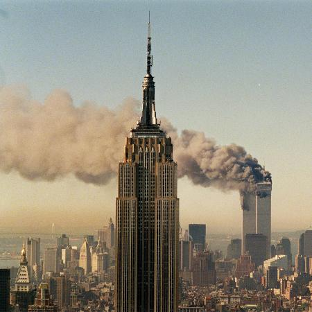 twin-towers-of-the-world-trade-center-burn-behind-the-empire-state-buildiing-september-11-2001
