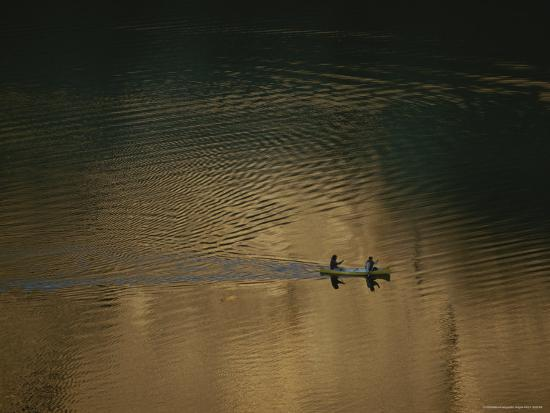two-men-paddle-a-canoe-on-a-smooth-body-of-water