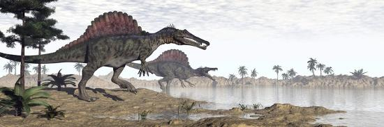 two-spinosaurus-dinosaurs-walking-to-the-water-in-a-desert-landscape