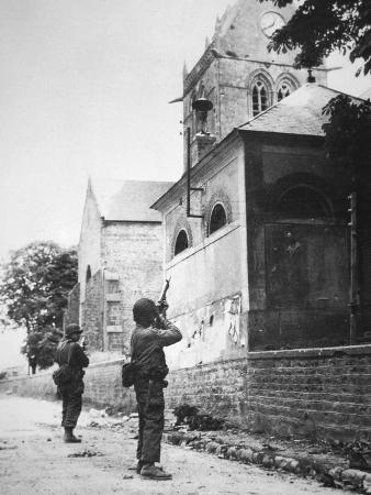 us-paratrooper-fires-into-church-steeple-at-sainte-mere-eglise-to-clear-enemy-sniper-6th-june-1944