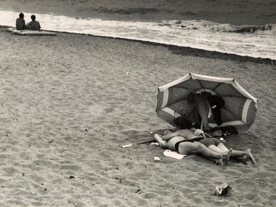 vincenzo-balocchi-young-couple-in-an-amorous-embrace-lying-on-the-beach-on-the-seashore