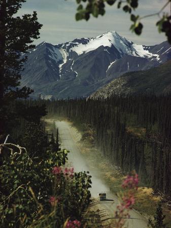 w-e-garrett-a-camper-rolls-down-a-dirt-road-below-high-mountains-in-alaska