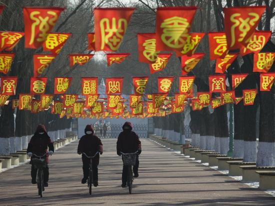 walter-bibikow-bicycle-riders-at-entranceway-to-festival-ice-and-snow-festival-harbin-heilongjiang-china