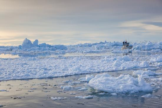 walter-bibikow-greenland-disko-bay-ilulissat-fishing-boat-in-floating-ice-at-sunset