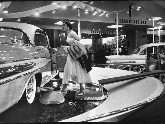 walter-sanders-model-gingerly-traversing-stepping-stones-to-get-to-la-parisienne-pontiac-hard-top-car-on-display