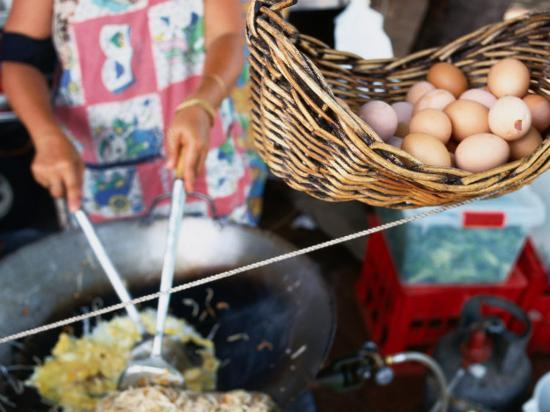will-salter-basket-of-eggs-hanging-in-front-of-woman-cooking-asian-stir-fry-rapid-creek-market-australia