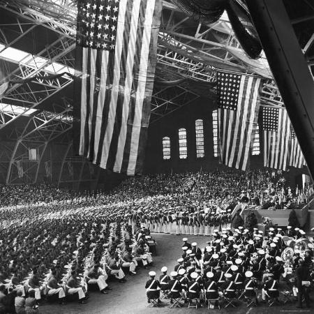 william-c-shrout-graduating-cadets-receiving-commissions-us-flags-hanging-above-during-the-graduation-ceremonies