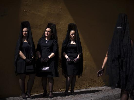 women-wearing-the-traditional-mantilla-in-front-of-la-macarena-church-in-seville-spain