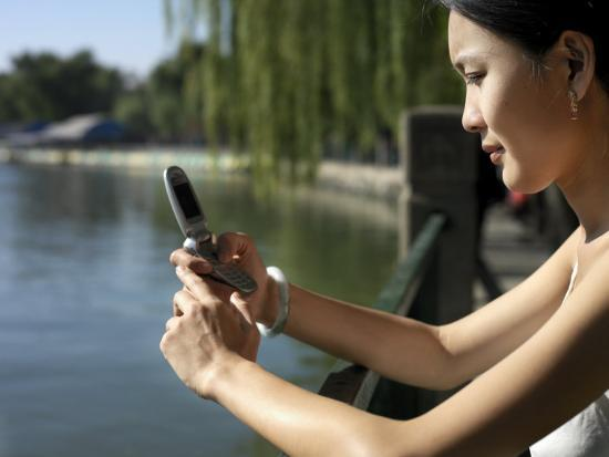 xpacifica-young-chinese-woman-checking-her-mobile-phone-in-beihi-park