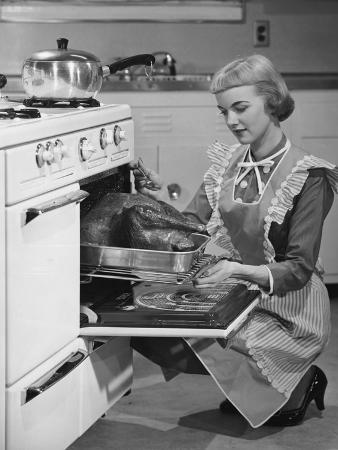 young-woman-putting-turkey-into-oven