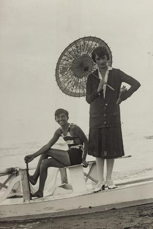 young-woman-with-umbrella-and-boy-on-pedal-boats-on-the-beach-of-forte-dei-marmi