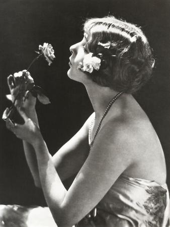 https://imgc.artprintimages.com/img/print/profile-view-of-young-woman-smelling-flower_u-l-q1bwge10.jpg?p=0