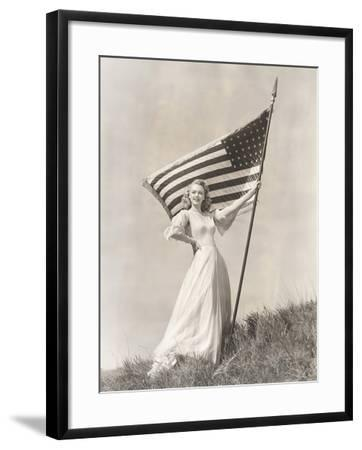 Proud Woman in Gown Holding American Flag on Hill--Framed Photo