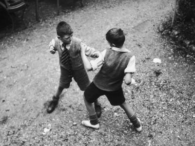 Put 'Em Up!' Two Boys Enjoy a Game of Fisticuffs in a Garden or Playground