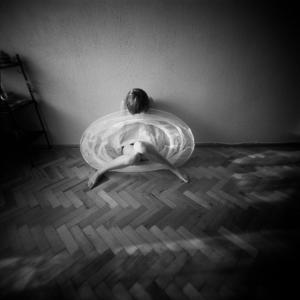 A Young Woman Sitting on a Pargued Floor by Rafal Bednarz