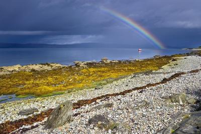 Rainbow Above Rocky Beach and Small Boat--Photographic Print