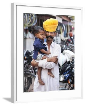 Rajasthani Man and His Son Waiting for Chai Near Local Motorcycle Shop-April Maciborka-Framed Photographic Print