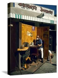 """Artist Ed Kienholz Drinking Coffee Inside Section of His Assemblage """"The Beanery. """" by Ralph Crane"""