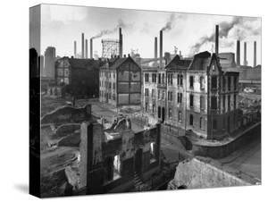 August Thyssen Steel Mill, Large Steel Works, Looming Smokily Behind Bomb-Ruined Town by Ralph Crane