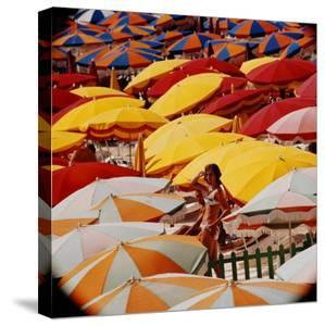 Europe Beach Scene Crowded with Colorful Umbrellas and a Bikini-Clad Young Woman by Ralph Crane