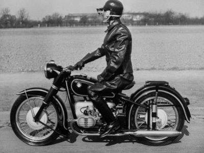 German Made BMW Motorcycle with a Rider Dressed in Black Leather by Ralph Crane