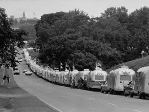 Long Line of Airstream Trailers Wait for Parking Space at a Campground During a Trailer Rally by Ralph Crane