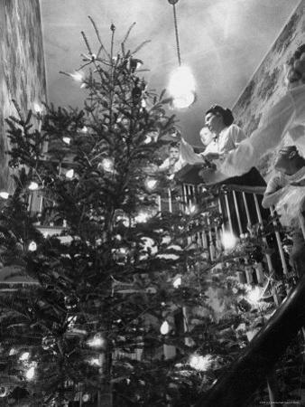 Mrs. George Sutton and Her Family Decorating Their Christmas Tree at Home by Ralph Crane