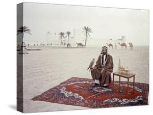 Sheikh Shakhbut Bin Sultan Al Nahyan Sitting in Front of His Palace Holding a Falcon, 1963 by Ralph Crane