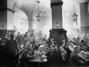 The Hofbrauhaus with Patrons Sitting at Long Tables Holding Large Steins of Beer by Ralph Crane