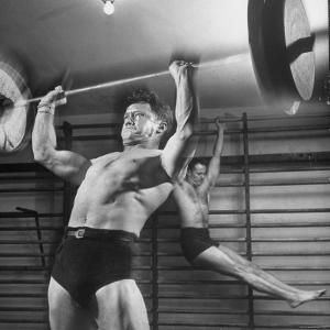 Weightlifter Charlie Morris at Southtown YMCA Working Out While Bob Byerwalter Works on Stall Bar by Ralph Crane