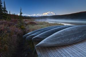 Canoes Lined Up on a Dock at Wonder Lake in Front of Mt. Mckinley by Ralph Lee Hopkins
