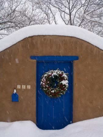 Snow Covered Christmas Wreath Adorns a Blue Door in Santa Fe