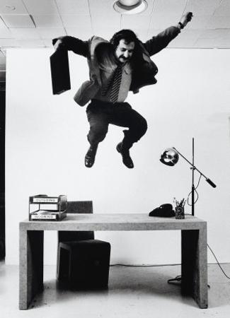 Architect and Designer Frank Gehry Jumping on a Desk in His Line of Cardboard Furniture by Ralph Morse