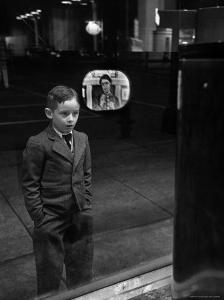 Boy Watching TV on Store Window Set, Glass Reflects the Image Off TV Screen by Ralph Morse