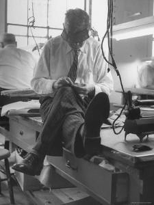 Custom Tailor Ernest Preedik Sitting on Table and Working in Factory by Ralph Morse