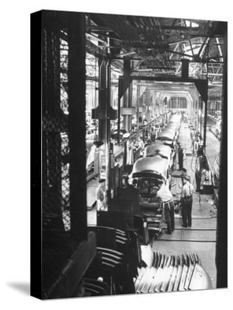 Employees Working on Cars as They Move Down Assembly Line