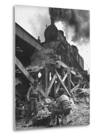Gi Infantry Guards Keeping Warm by a Fire Next to an Army Engineer Built Railroad Bridge