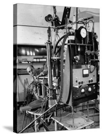 Italian Physicist Enrico Fermi Peering Out from Behind Large, Complicated Machinery in Laboratory