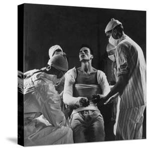 Mortar Wounded Army Medic Private George Lott, Sitting Up While 4 Army Surgeons Finish Up His Cast by Ralph Morse