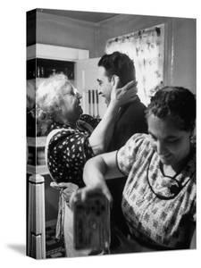 Mrs. Alfonso La Falce Kissing Baby Son at Family Reunion Dinner by Ralph Morse