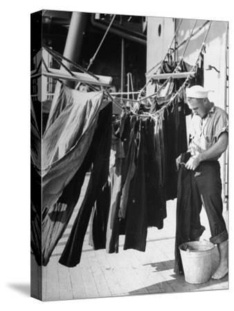 Sailor Aboard a Us Navy Cruiser at Sea Hanging Up Laundered Dungarees During WWII