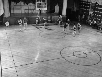 St. John's Basketball Team Members Practicing While their Coach Looks On