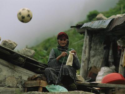 A Soccer Ball Flies over the Head of Woman Who is Knitting Outdoors