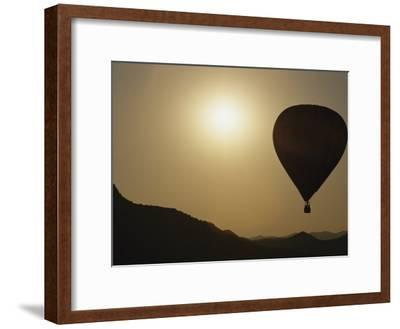 A Hot Air Balloon Rises Above a Hilly Landscape at Sunrise