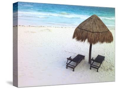 A Palm Frond Umbrella and Two Chairs on a White Sand Beach by Raul Touzon