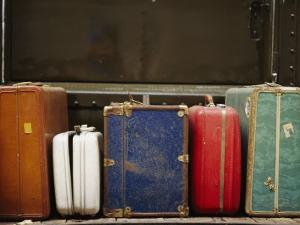 Colorful But Worn Luggage Awaits Travelers in a Train Station by Raul Touzon
