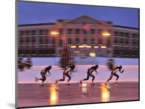 Ice skaters at dusk. by Raul Touzon