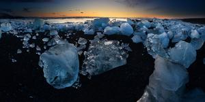 Pieces of glacial ice over black sand being washed by waves, Iceland by Raul Touzon