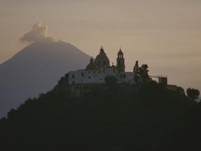 Popocatepetl Volcano Rises Behind a Hilltop Church in Cholula by Raul Touzon