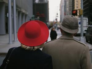 Rear View of Two People Wearing Hats Stopped at a Crosswalk by Raul Touzon